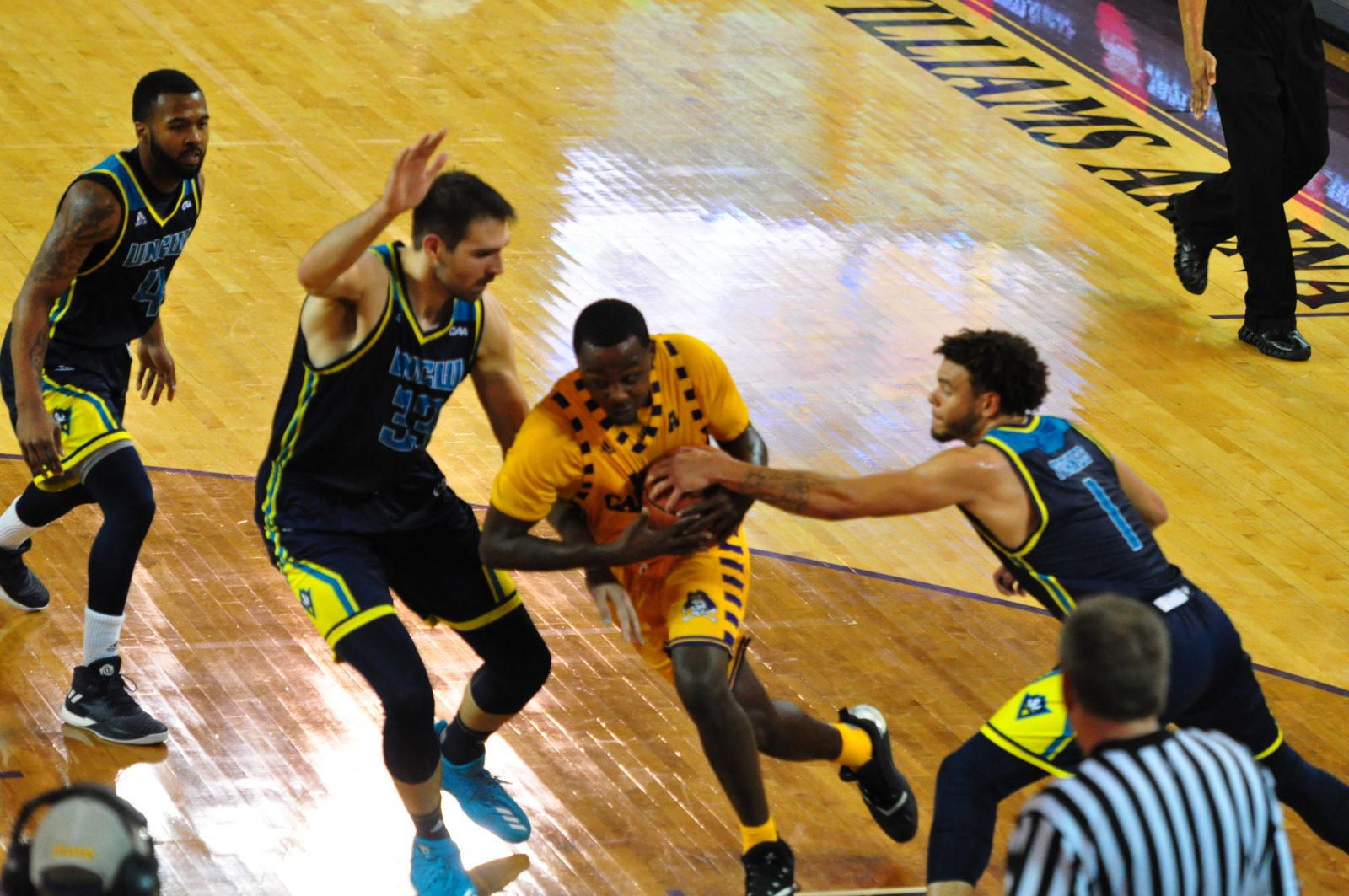 Pirate guard Isaac Fleming appears to have found a hole in the UNCW defense and makes like a running back. (Photo by Al Myatt)