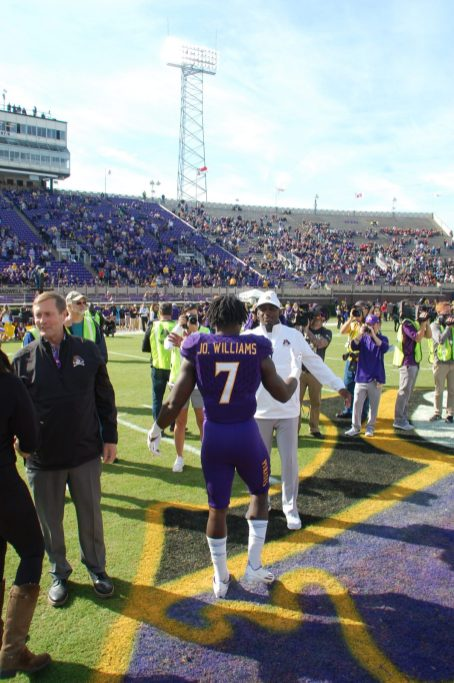 Senior linebacker Jordan Williams steps forward for a hug from ECU coach Scottie Montgomery.