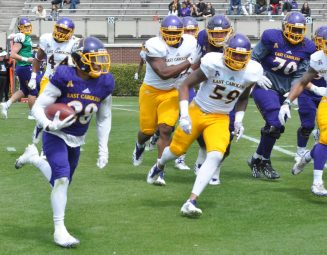 Hussein Howe carries the ball for the Purple with sophomore defensive end Chandon Hickerson (59) in pursuit for the Gold. (Photo by Al Myatt)