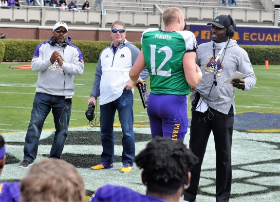 Quarterback Holton Ahlers, an early enrollee from nearby D.H. Conley, receives the Top Offensive Newcomer award from coach Scottie Montgomery at halftime of the Purple-Gold game. In the background are Daren Hart (left) and Jim Bolding. Hart was honorary coach for the Gold and Bolding was honorary coach of the Purple. Both were standouts in the secondary for East Carolina. (Photo by Al Myatt)