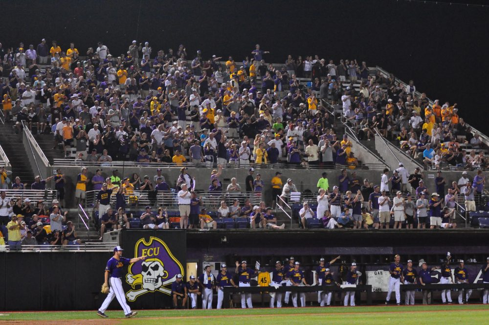 The third base side of Pirate Nation celebrates a leaping catch against the wall in dead centerfield by Drew Henrickson. Despite the four-hour delay in start time, Pirate fans filled Clark-LeClair stadium until the final out at roughly 12:34 a.m. Sunday Morning. (Photo by W.A. Myatt)