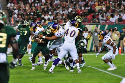 Defensive tackle Alex Turner swallows USF running back Jordan Cronkrite for a loss. (Photo by W.A. Myatt)
