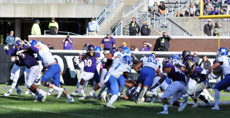 #3 of 3-photo sequence: Although the Pirates and Coach Montgomery were vocal about blatant holding, the ECU defender, his number obscured by the blocker's grasp of his jersey, was ridden out of this play and there was no call. (Photo by Al Myatt)