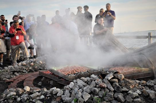 Steam rises as the cover is pulled away from the food that was cooked below ground. (Photo by Al Myatt)