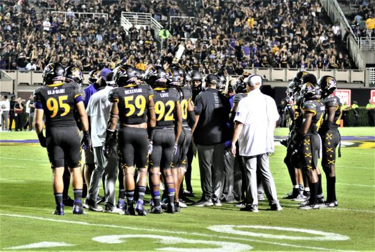 The Pirates huddle up during a timeout before making a third-down stop. (Photo by Al Myatt)