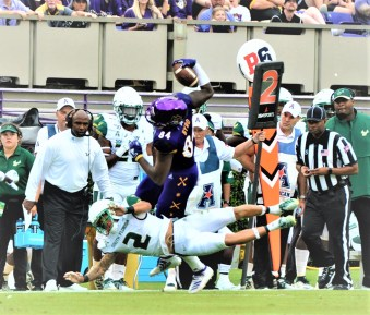 Zech Byrd makes a 5-yard gain on a catch for East Carolina as Nick Roberts (2) makes the stop in front of USF coach Charlie Strong. (Photo by Al Myatt)