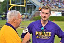 Sideline announcer Brian Bailey talks to former Pirate kicker Jake Verity, ECU's leading career scorer. (Al Myatt photo)