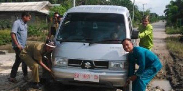 Jalan Depan Kantor Rusak Kembali, Penghulu Kampung Jatibaru Beserta Staf Bantu Dorong Mobil Terpuruk