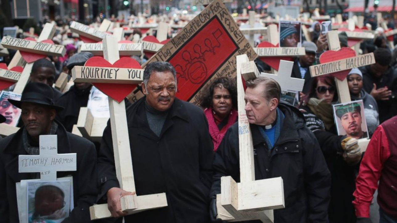 The Rev. Jesse Jackson (L) and Rev. Michael Pfleger carry crosses as they march with other residents, activists, and family members of victims of gun violence down Michigan Avenue, Dec. 31, 2016 in Chicago. (Scott Olson/Getty Images)