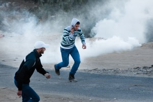 EAST JERUSALEM - DECEMBER 3, 2010: Palestinian youth flee tear gas fired by Israeli police in clashes in the streets of the Al-Issawiya neighborhood protesting the demolition of homes by Israeli authorities.