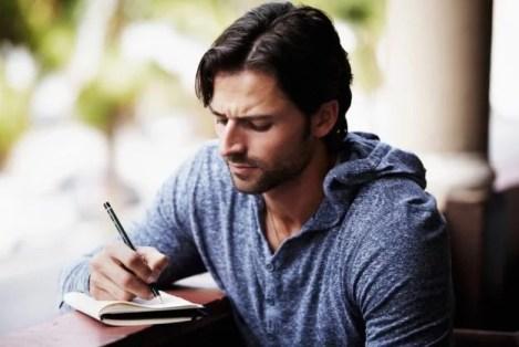 un bel homme écrivant une carte postale