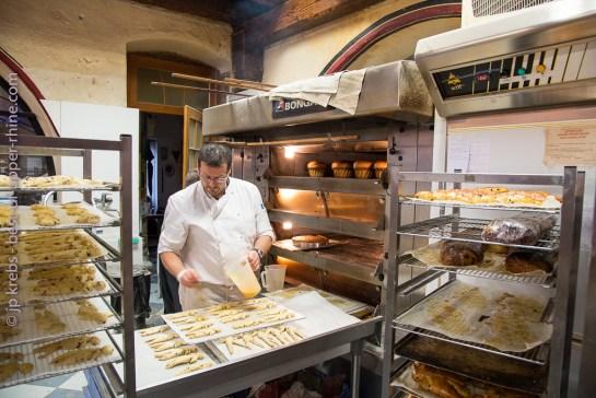 Préparation des mannalas. Avant d'enfourner les petits bonhommes de Saint-Nicolas, le boulanger les badigeonne de jaune d'œuf pour qu'ils soient bien dorés. Maison du Pain à Sélestat.