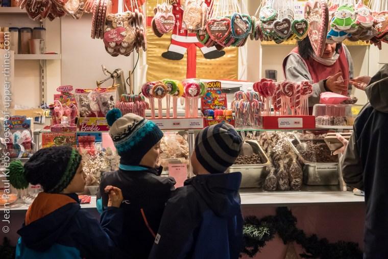 Enfants se régalant de friandises au marché de Noël de Bâle.