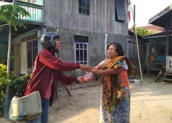 BAGIKAN DAGING KURBAN: Pengurus AJKT membagikan daging kurban kepada warga Kampung Kajang.(Dhedy/ Sangatta Post)