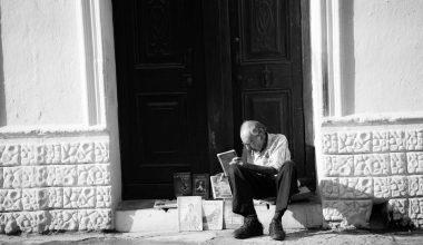 man sitting on white tile floor near door
