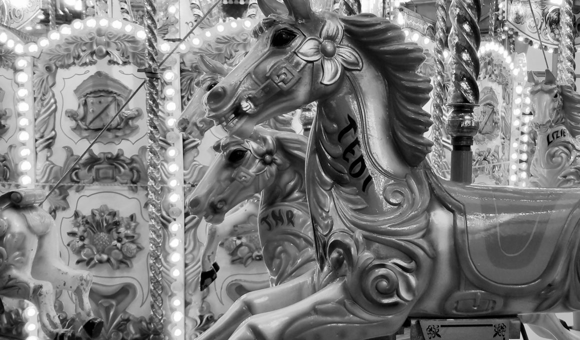 white horse carousel with people