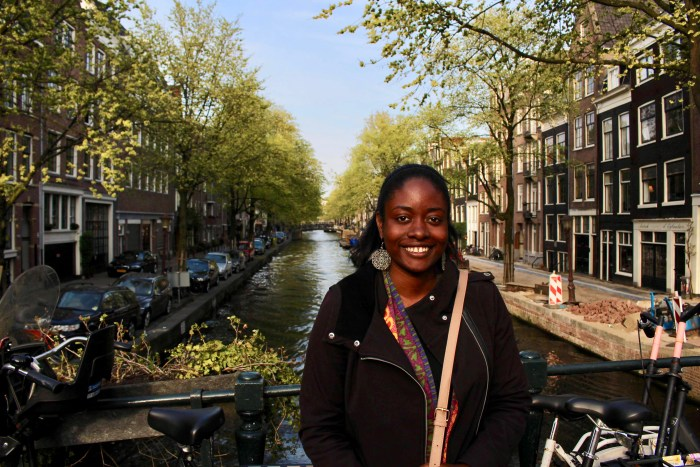 Young black woman smiling in front of a canal in Amsterdam.