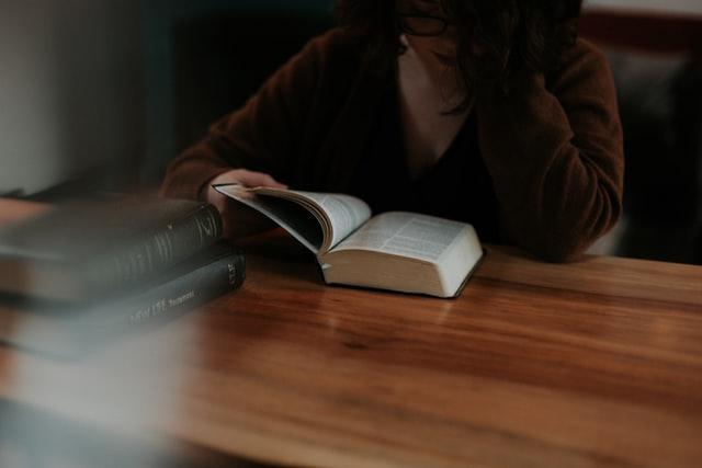 صورة لفتاة أمام كتاب مقدس ترمز لاقتباس من كتاب النبي لجبران خليل جبران