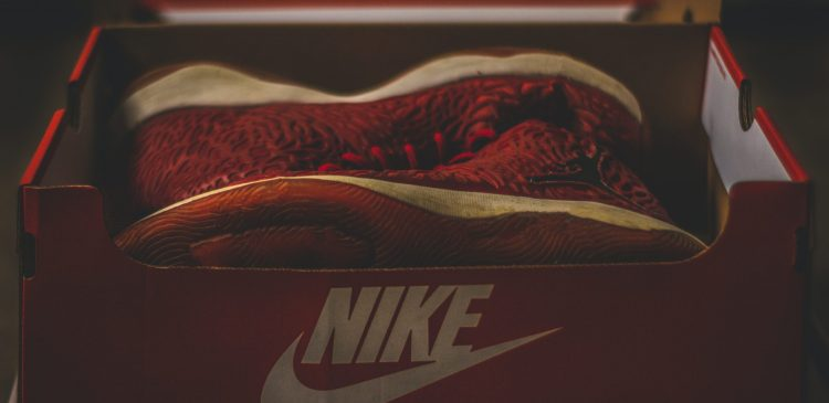Shoe box with a pair of red nike shoes inside.