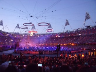 The Olympic rings come together above the stadium