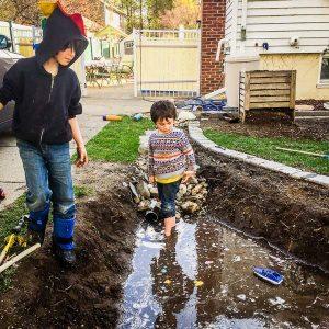 kids play in freshly dug rain garden