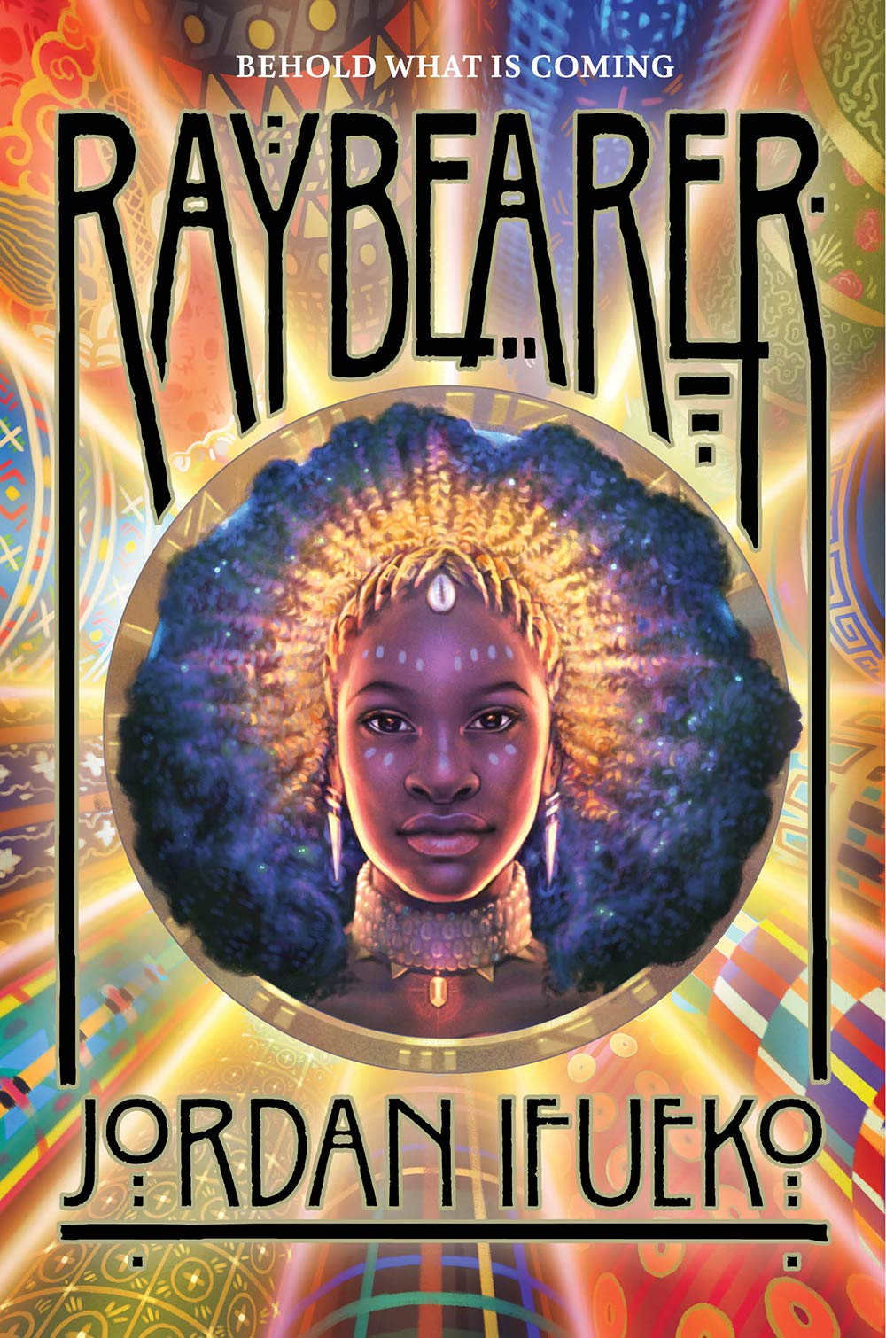 It's the cover of the book. At the very top of the image there's the title (Raybearer) in black while at the very bottom there's the author's name (Jordan Ifueko). The background is a pattern made up of different coloured rays (some gold, some red, some blue) whereas in the middle there is an image of a young black woman with her black hair fanned out around her. On her head she is wearing a golden tiara in the shape of rays that emanate out.