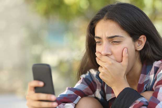 teenager_looking_at_cell_phone_sextortion_stock_image-100577580-large