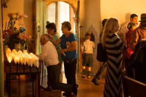 Parishioners pray following a mass at Mission San Juan Bautista. (Reinforcing community bonds.)
