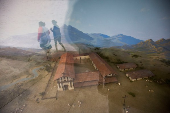 Visitors to Mission San Francisco de Asís are reflected in the glass of a model demonstrating what the grounds of the mission might have looked like during the height of religious conversions, early 19th c.