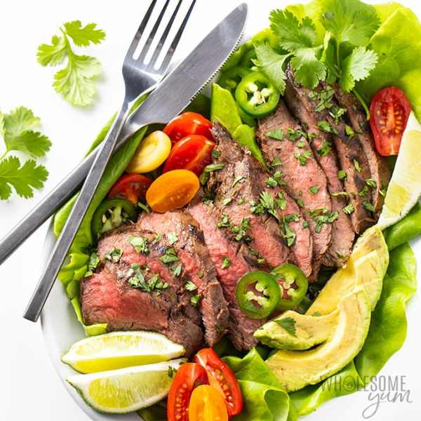 sliced steak on top of butter lettuce leaves with tomatoes and lime slices on the side