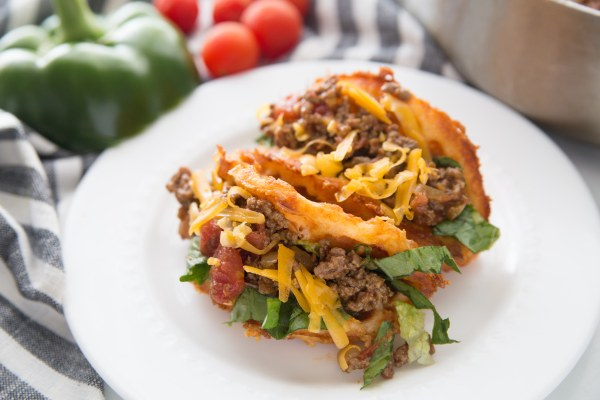 crispy keto taco chaffles filled with ground meat and cheese on a white plate