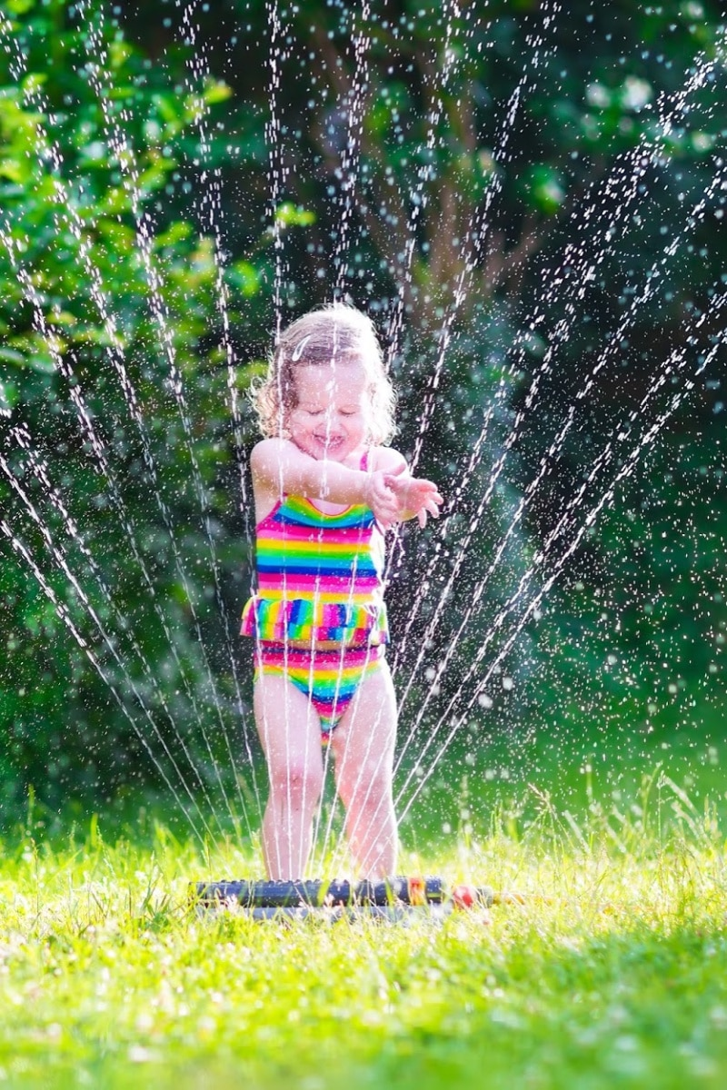 little girl in a colorful bathing suit playing in a sprinkler outside