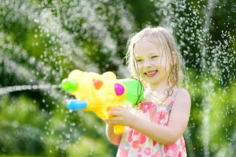 little girl outdoor playing a water game with a water gun