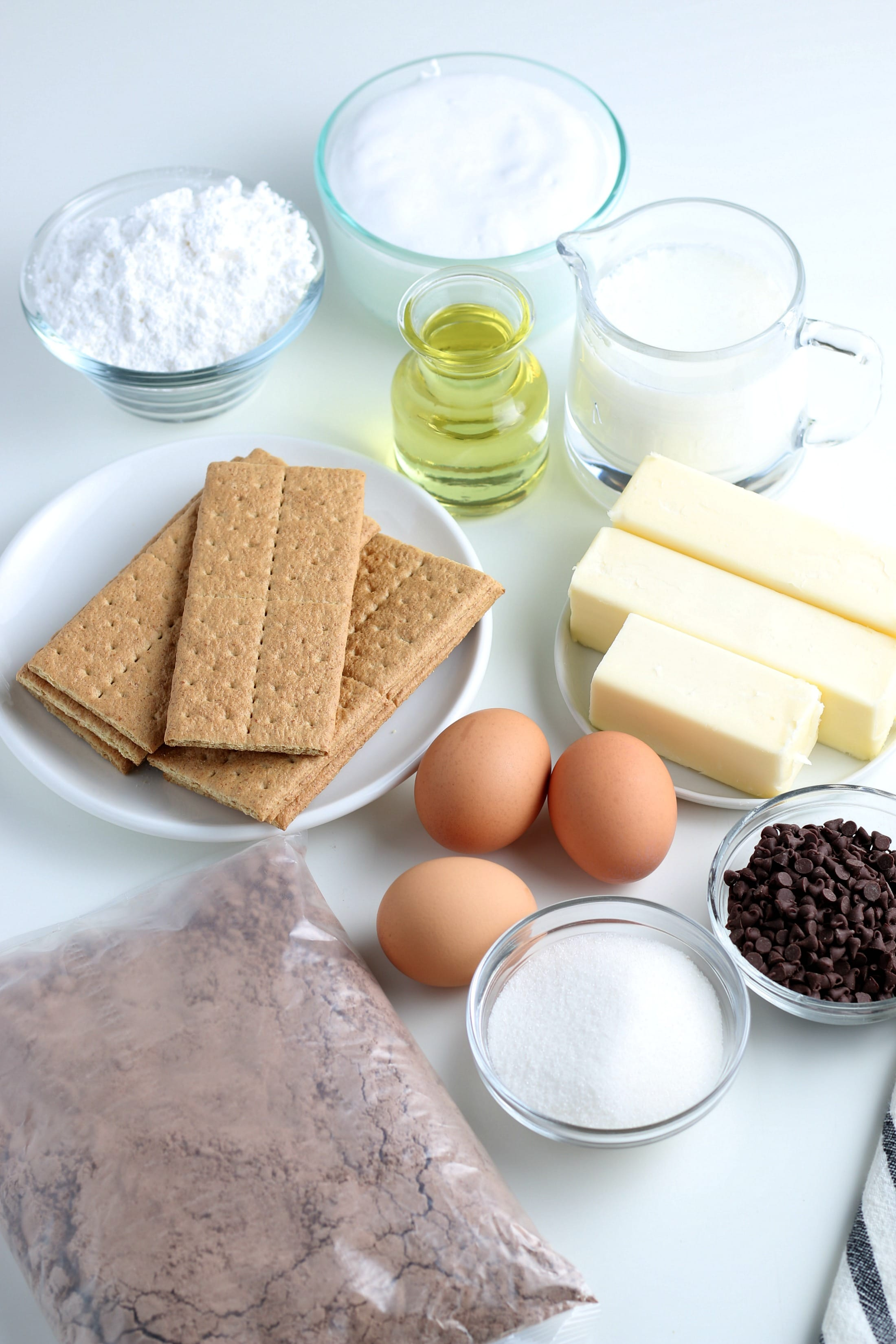 ingredients for s'mores cupcakes laying out on a white countertop.