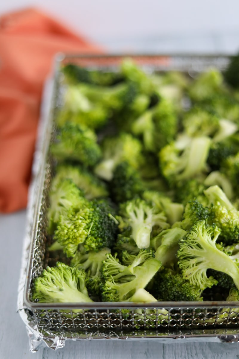 Broccoli florets in air fryer basket