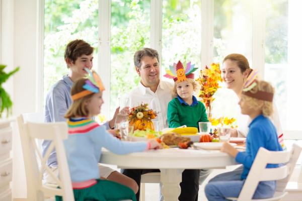 Family with kids eating Thanksgiving dinner. Roasted turkey and pumpkin pie on dining table with autumn decoration.
