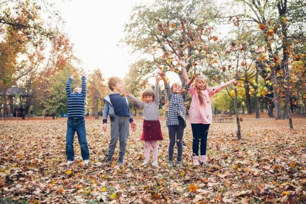 Happy kids playing with autumn leaves and having fun in park.