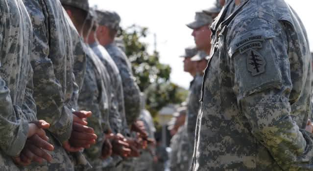 Soldiers stand in formation, preparing to don their Green Berets for the first time, during a Regimental First Formation ceremony. (Photo provided by USAJFKSWCS Public Affairs)