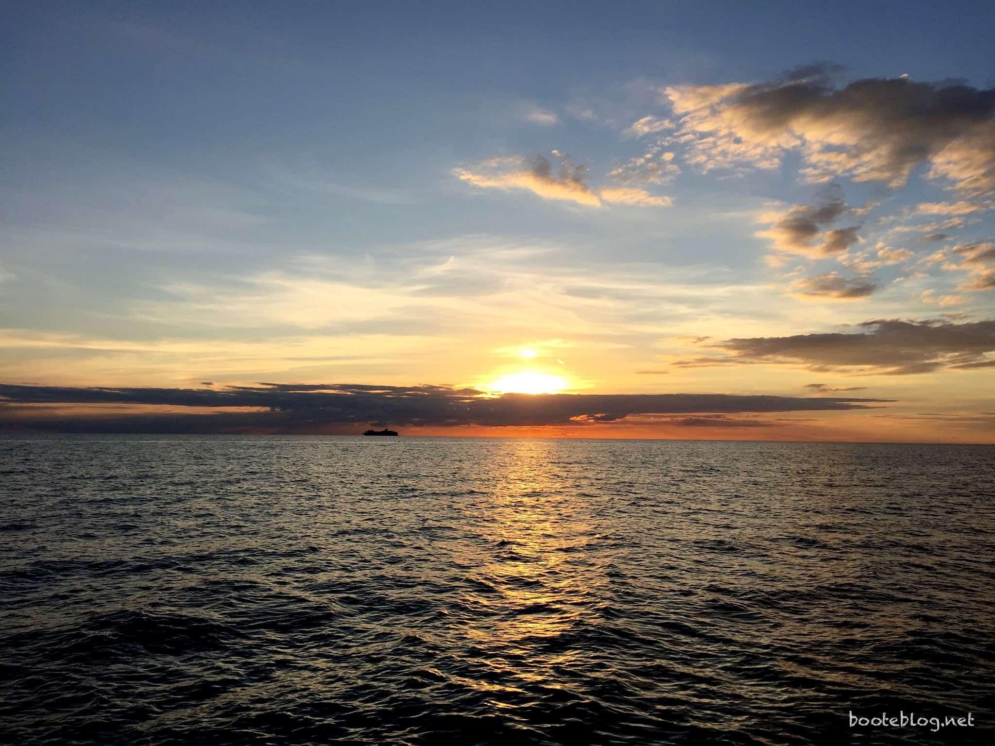 Sonnenuntergang im Kattegat. Am Horizont ist die Silhouette eines Kreuzfahrschiffs zu erkennen.