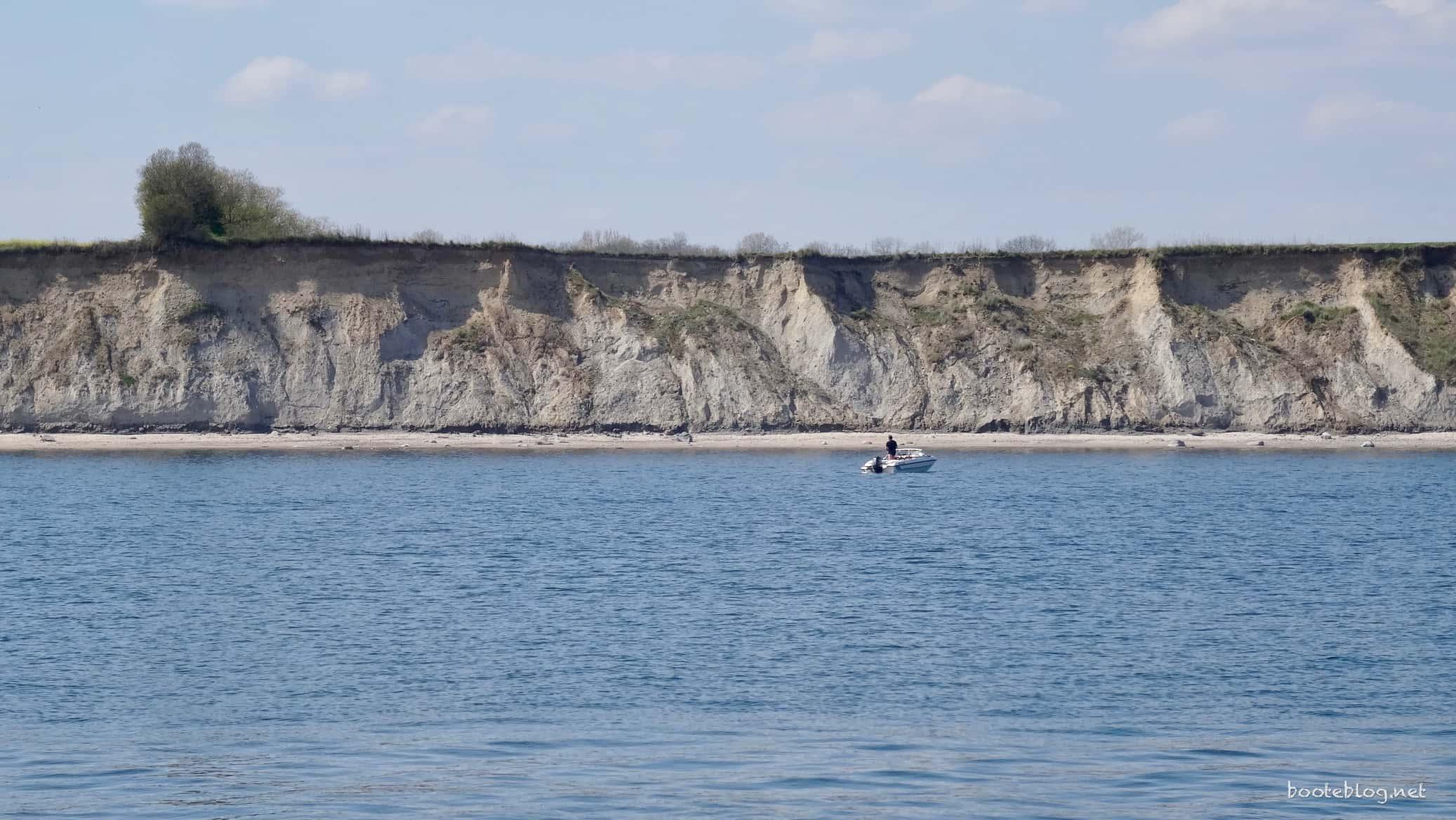 Ein Angler, der im kleinen Boot entspannt vor der Küste ankert.