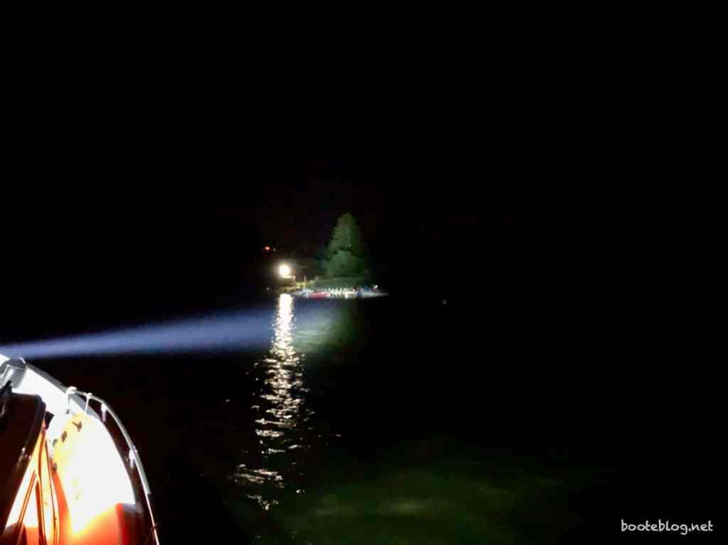 Suchscheinwerfer auf dem Boot leuchtet das Ufer an.
