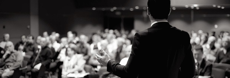 Un homme prend la parole lors d'une conférence face à un public