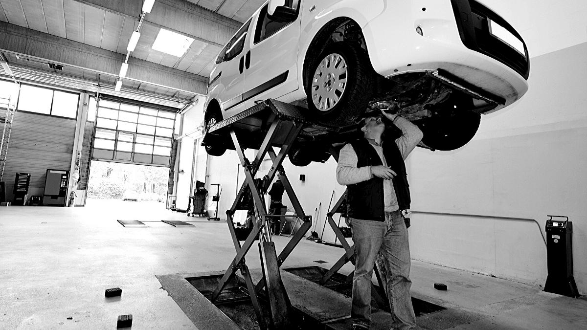 mécanicien faisant des réparations automobiles sur une voiture blanche dans un garage à Bordeaux