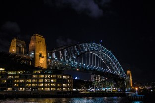 The harbour bridge at night. Above the lights at the top of the bridge there is a constant vortex of gulls eating the insects attracted by the lights.
