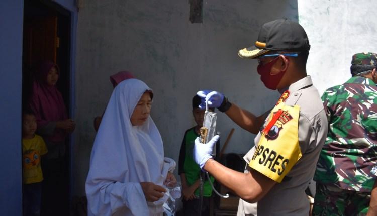 NEWS: Kapolres Magelang AKBP Pungky Bhuana Santoso saat hendak memberikan dan mengenakan masker ke salah satu warga di Salaman (9/4/2020)-(Foto: Istimewa)
