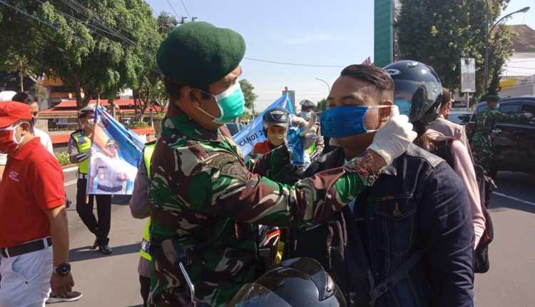 OPERASI: Prajurit Yonarmed 11 membagikan masker gratis bagi pengendara yang melintas di depan Alun-alun Magelang, Sabtu (18/4). (Foto: mta)