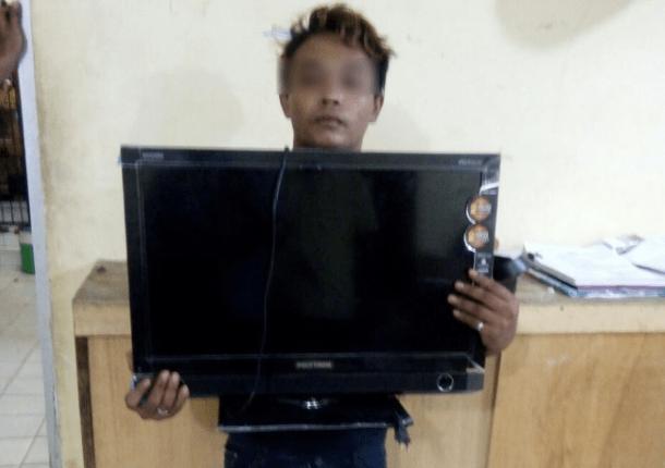 ELEKTRONIK: Seorang pencuri menunjukkan televisi yang ia curi (gambar: ilustrasi)