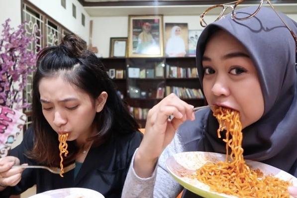 NENDANG LIDAH: 2 gadis cantik makan mie terpedas di dunia. (foto: ist)