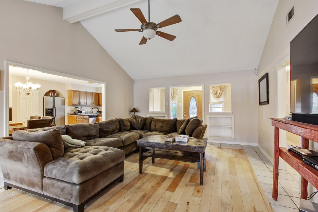 Vaulted ceiling with ceiling fan, wood floors, white and beige walls, with a large wraparound couch and coffee table placed in the center of the room.