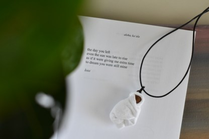 necklace with baby pendant lying on top of poetry about miscarriage